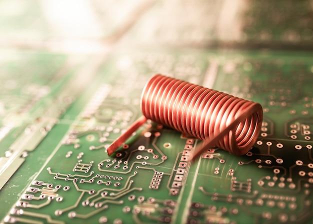 Skręcony drut miedziany leży na zielonym chipie. koncepcja sprzętu komputerowego. fabryka do produkcji laptopów i technologii cyfrowej
