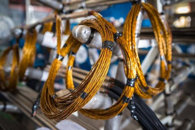 Skręcony drut miedziany zawieszany jest na metalowych stojakach przy produkcji dużych części przemysłowych oraz w przemyśle maszynowym i stoczniowym. koncepcja części zamiennych i części do sprzętu elektronicznego