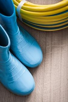 Skręcony wąż ogrodowy i wodoodporne gumowe buty na drewnianej powierzchni