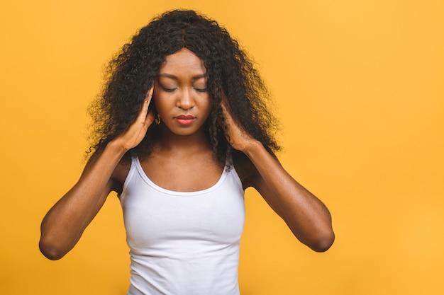 Skrępowana młoda afroamerykańska kobieta zaciska oczy i masuje palcami skronie