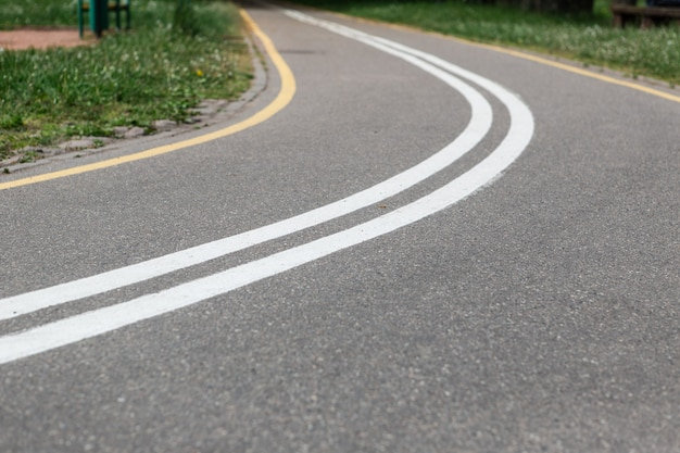 Skręt ścieżki rowerowej w wiosennym parku. pusta droga.