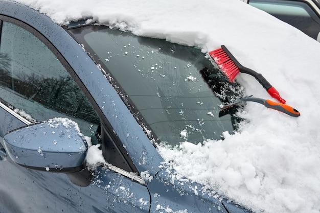Skrobaczka do lodu i szczotka do czyszczenia samochodu znajdują się na masce samochodu