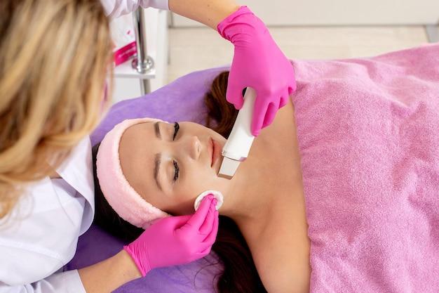 Skrobanie ultradźwiękowe. młoda kobieta otrzymująca ultradźwiękowy peeling kawitacyjny do oczyszczania twarzy. kosmetologia oczyszczająca zabieg pielęgnacyjny skóry twarzy. ręce kosmetyczki w pracy, oczyszczające skórę strumieniem wody.
