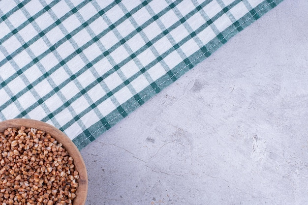 Skromna miska gryki na ręczniku rozłożonym na marmurowym tle. zdjęcie wysokiej jakości
