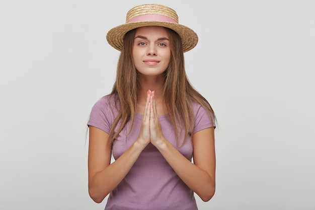 Skromna młoda kobieta w słomkowym kapeluszu modli się o dobre samopoczucie