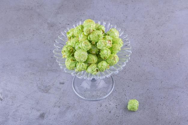 Skromna porcja smakowego zielonego popcornu na szklanym pojemniku na cukierki na marmurowym tle. zdjęcie wysokiej jakości