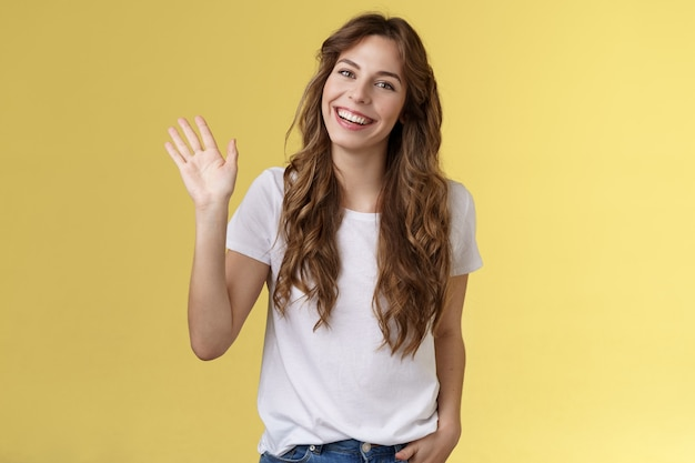 Skromna urocza przyjazna wychodząca atrakcyjna europejska kobieta długa kręcona fryzura macha dłonią towarzyska rozmowa przedstawia się uśmiechnięta szeroko powiedzieć cześć pozdrowienie współpracownika żółte tło.