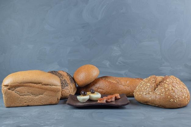 Skromny zestaw śniadaniowy otoczony bochenkami chleba na marmurowym stole.