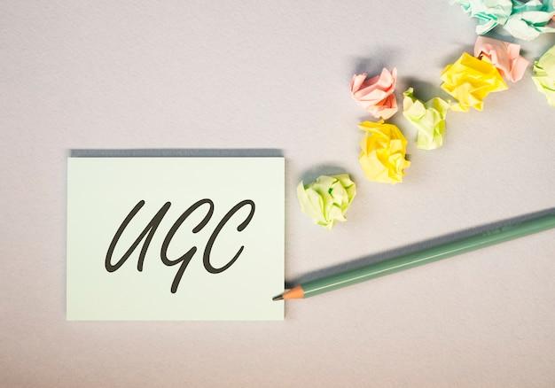 Skrót ugs lub user-generated content oznaczający media społecznościowe na kolorowych, jasnych karteczkach samoprzylepnych z pogniecionymi papierami.