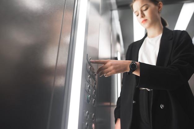 Skrupulatna bizneswoman wciska guzik w windzie z zegarkiem na nadgarstku.