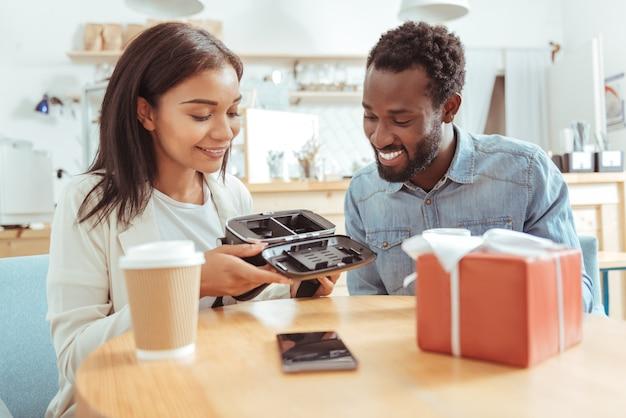 Skrupulatna kontrola. ładna młoda kobieta siedzi przy stoliku w kawiarni ze swoim najlepszym przyjacielem i razem uważnie ogląda swój nowy zestaw vr