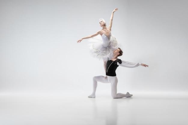 Skrzydełka. pełen wdzięku tancerzy baletu klasycznego, taniec na białym tle na tle białego studia. para w delikatnych białych ubraniach jak postacie z białych łabędzi. koncepcja łaski, artysty, ruchu, akcji i ruchu.