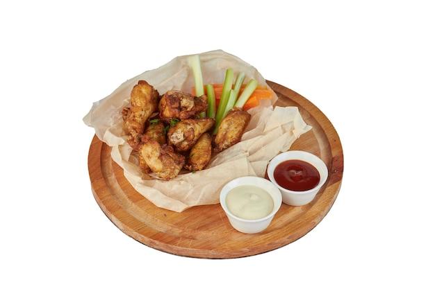 Skrzydełka z kurczaka buffalo na talerzu z sosem, marchewką i selerem