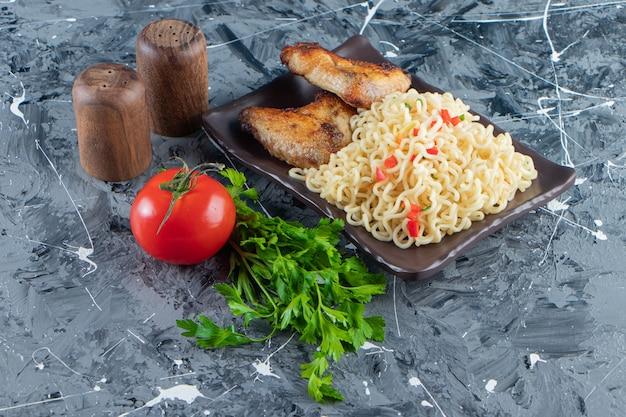 Skrzydełka z kurczaka i makaron na półmisku obok warzyw, na marmurowej powierzchni.