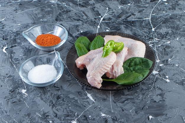 Skrzydełka z kurczaka i szpinak na talerzu obok misek na przyprawy i sól, na marmurowej powierzchni.