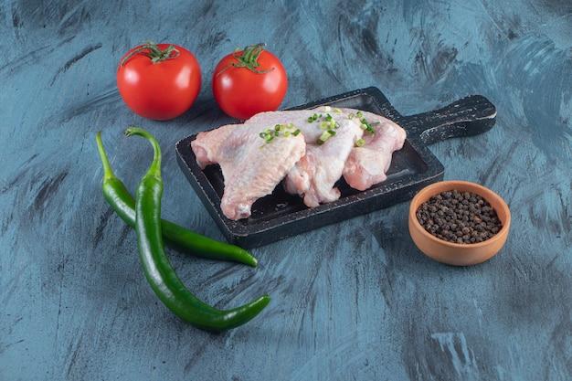Skrzydełka z kurczaka i warzywa na desce, na niebieskiej powierzchni.