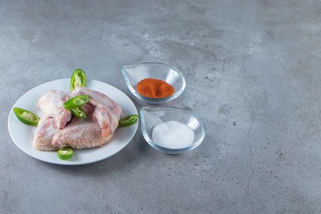 Skrzydełka z kurczaka na talerzu obok misek na przyprawy i sól, na marmurowym tle.