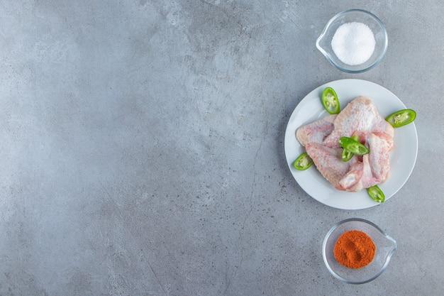 Skrzydełka z kurczaka na talerzu obok misek z przyprawami i solą, na tle marmuru.