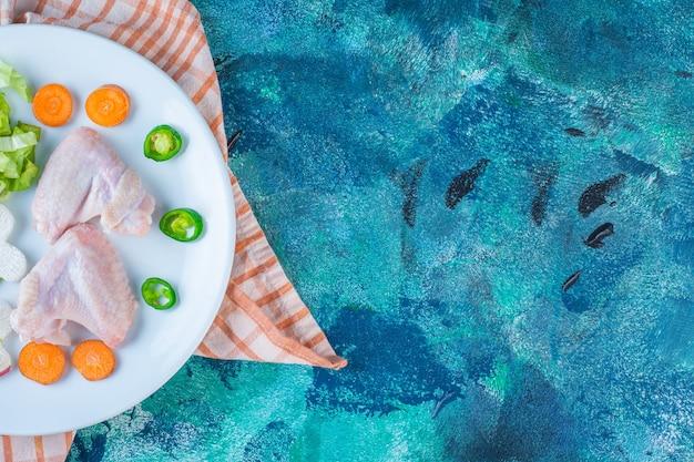 Skrzydełka z kurczaka, pietruszka, marchewka i papryka na talerzu na ściereczce