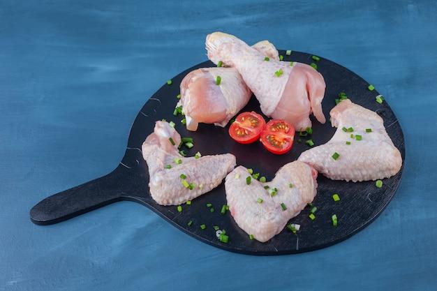 Skrzydełka z kurczaka, podudzia na desce do krojenia, na niebieskim stole.