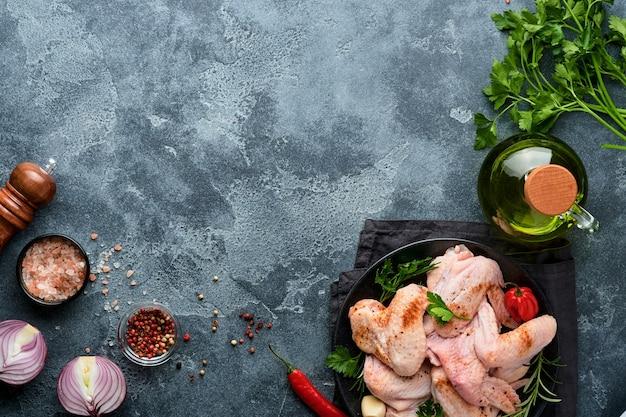 Skrzydełka z kurczaka surowego w metalowej patelni lub misce z przyprawami i składnikami do gotowania na ciemnoszarym tle łupków, kamienia lub betonu. surowe mięso z przyprawami na czarnym stole. widok z góry. makieta.