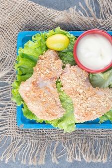Skrzydełka z kurczaka z bułką tartą i warzywami na niebieskim talerzu.