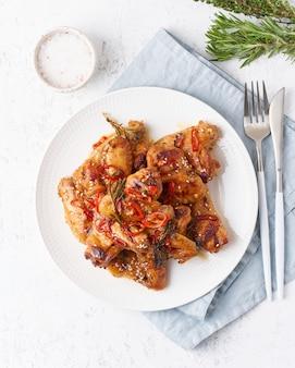 Skrzydełka z kurczaka z grilla. kurczak pieczony na talerzu w czerwonym sosie. gorące azjatyckie jedzenie. widok z góry