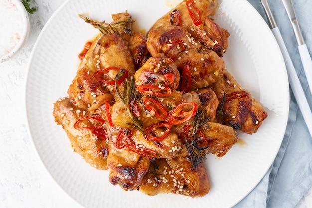 Skrzydełka z kurczaka z grilla. wolnowar słodki i pikantny. piec upieczony marynowany kurczak na talerzu