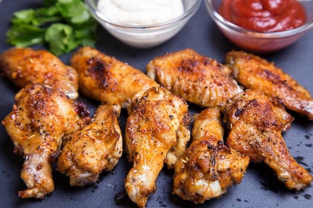 Skrzydełka z kurczaka z grilla z dwoma sosami na czarnej desce. zbliżenie. selektywne ustawianie ostrości.