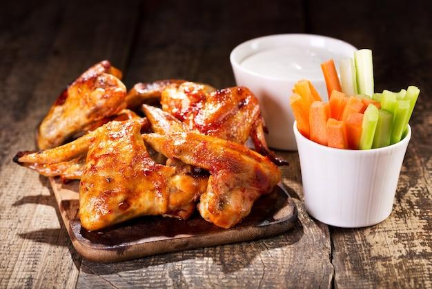 Skrzydełka z kurczaka ze świeżymi warzywami i sosem na drewnianym stole