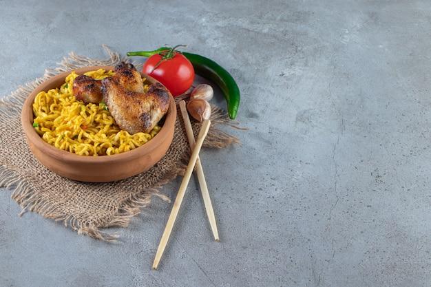 Skrzydełko i makaron w misce na płótnie obok warzyw i pałeczek na marmurowym tle.