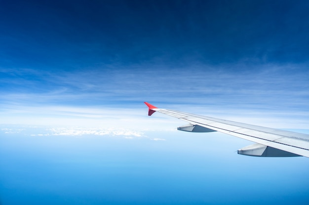 Skrzydła samolotu na tle malutkiego chmurnego nieba