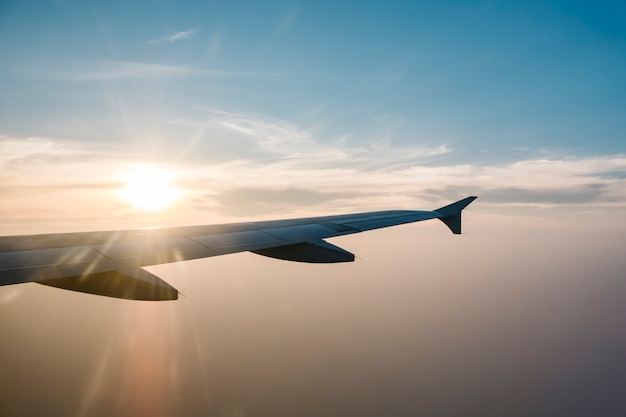 Skrzydło samolotu i zachód słońca na niebieskim niebie