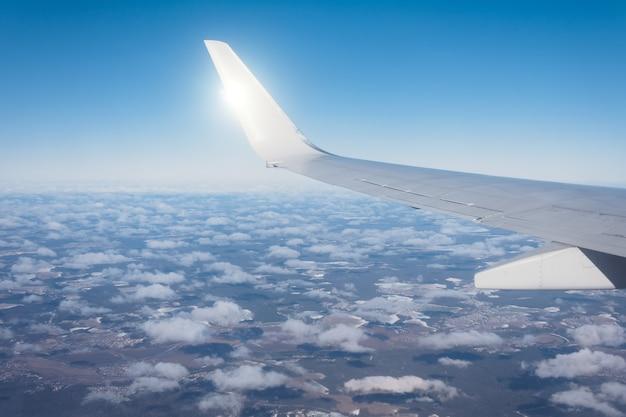 Skrzydło samolotu lecącego ponad chmurami, transport lotniczy do podróży. światło słoneczne z tyłu.