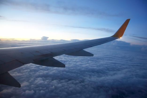 Skrzydło samolotu pasażerskiego w locie nad wieczornymi chmurami