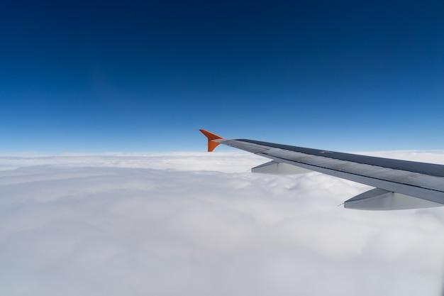Skrzydło samolotu ponad chmurami na bezkresnym niebie