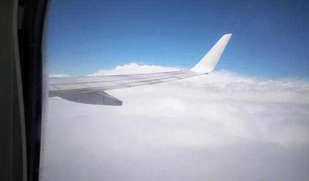 Skrzydło samolotu z okna samolotu. widok z samolotu na skrzydło na niebie nad chmurami. lot samolotem.