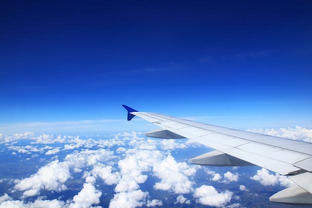 Skrzydło samolotu zobacz chmury na ciemnym niebie.