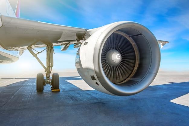Skrzydło silnika odrzutowego samolotu na parkingu na płycie lotniska w słoneczny dzień.