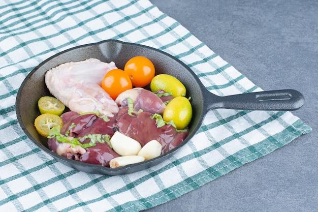 Skrzydło surowego kurczaka i świeże warzywa na czarnej patelni.