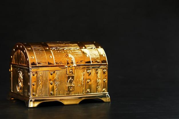 Skrzynia ze złota z klejnotami na czarnym tle. wolna przestrzeń, pojęcie bogactwa. niski klucz.
