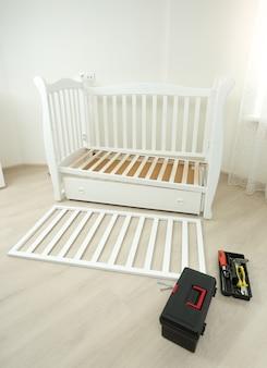 Skrzynka na narzędzia leżąca na podłodze obok zdemontowanego drewnianego łóżeczka