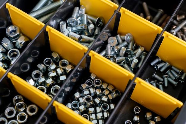 Skrzynka narzędziowa z komórkami ze śrubami, kotwami, gwoździami, śrubami i innymi narzędziami w warsztacie