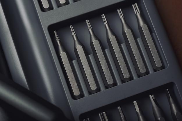 Skrzynka narzędziowa z metalowym śrubokrętem i kolekcją wymiennych zestawów bitów, głowica sześciokątna o różnej wielkości, wysokiej jakości narzędzia i sprzęt do naprawy.