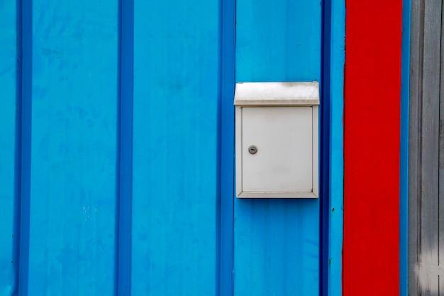 Skrzynka pocztowa na niebieskich drzwiach domu w mieście
