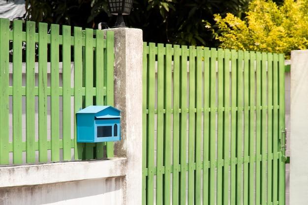 Skrzynka pocztowa przed domem i bramą z światłem słonecznym i pięknym naturalnym tłem
