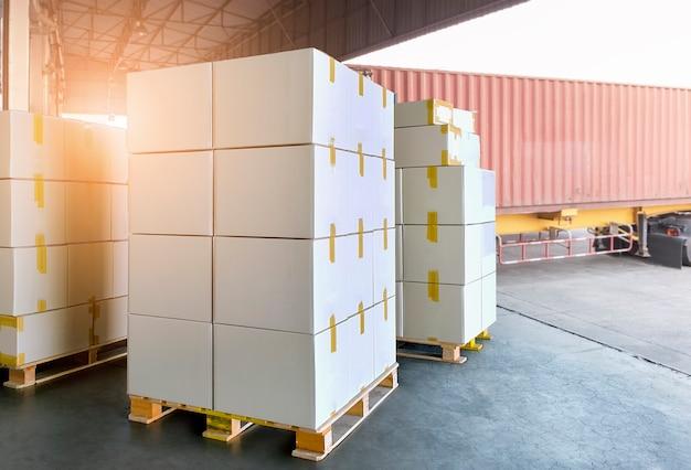 Skrzynki do przewozu ładunków. stos kartonów na paletach czekających na załadowanie do ciężarówki kontenerowej.