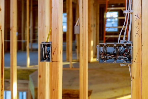 Skrzynki gniazd elektrycznych z drutami drewnianych belek w ścianie