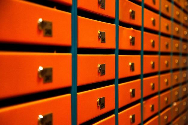 Skrzynki pocztowe orange w apartamentowcu. nawet rzędy numerowanych skrzynek pocztowych. koncepcja korespondencji w mieście. możesz go użyć jako tła dla swojej kreacji. skopiuj miejsce