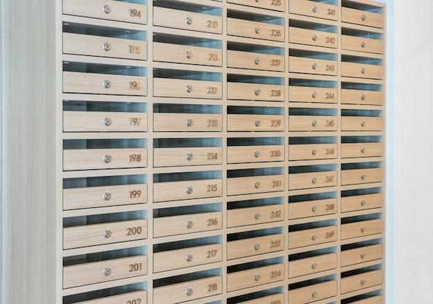 Skrzynki pocztowe wypełnione ulotkami i listami, skrzynki pocztowe i zamki w rzędach przy wejściu.